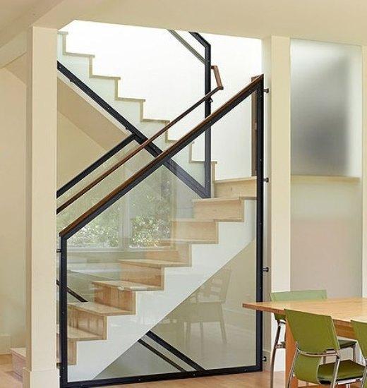 与楼梯扶手结合设计的梯形玻璃隔断,将每一阶楼梯紧紧包裹,给极简的